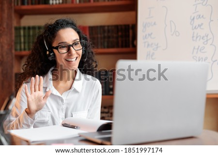 Distance Education. Positive lady wearing glasses and wireless headest at virtual meeting, sitting at desk, having video call on laptop, waving to webcam. Woman studying or teaching online at home Royalty-Free Stock Photo #1851997174