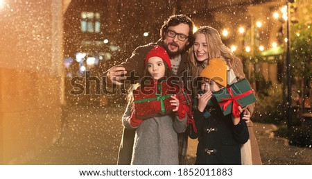 Cheerful Caucasian family taking funny pictures on smartphone together on snowy street on evening. Happy parents and kids taking selfie photos on cellphone in decorated xmas city