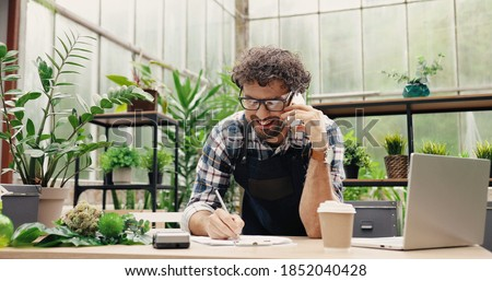 Happy Caucasian businessman talking on cellphone while standing in apron in small floral center and writing down order details. Joyful male florist calling on smartphone at work. Own business concept Royalty-Free Stock Photo #1852040428