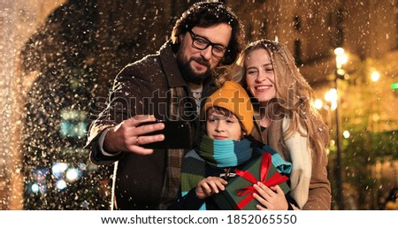 Portrait of happy Caucasian family taking funny pictures together on snowy street on evening on new years eve. Father, mother and small son taking selfie photos on cellphone in decorated xmas city