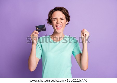 Photo of lovely lucky young lady wear casual teal outfit holding credit card hand arm fist closed eyes isolated purple color background