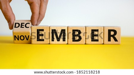 Symbol for the change from November to December. Male hand flips wooden cubes and changes the inscription 'november' to 'december'. Beautiful yellow table, white background, copy space. Royalty-Free Stock Photo #1852118218