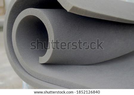 gray sponge foam roll in a spiral style.  foam sponge rubber texture sheet Royalty-Free Stock Photo #1852126840