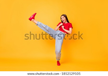 Full length photo focused girl practicing kicks raise leg exercise wear red crop top jeans isolated yellow color background Royalty-Free Stock Photo #1852129105