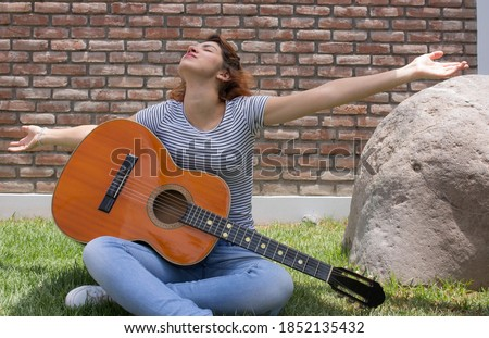 A beautiful Hispanic young woman playing her guitar against a brick wall background