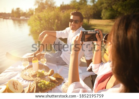 Woman taking picture of boyfriend on pier at picnic, closeup