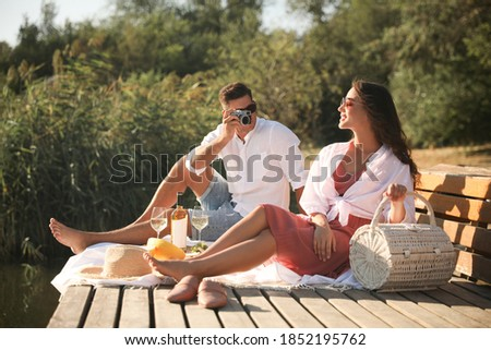 Man taking picture of girlfriend on pier at picnic