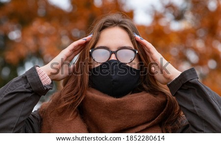 The woman wears a black mask due to the pandemic, but her glasses are fogged up. The problem of fogging glasses due to wearing a surgical mask. Royalty-Free Stock Photo #1852280614