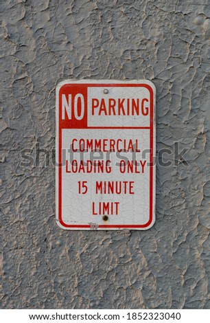 Old commercial no parking sign on a gray stucco wall in the early morning light.