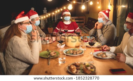 Multiracial senior people celebrate christmas together with dinner outdoor while wearing safety mask for coronavirus outbreak - Soft focus on african woman face #1852328770