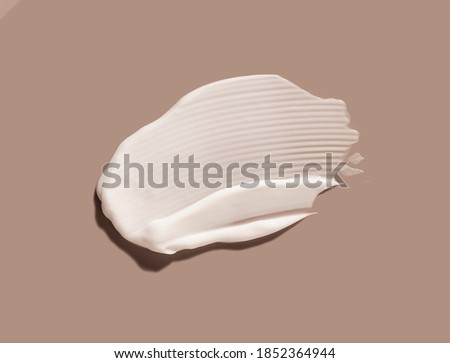 Liquid cream cosmetic smudge texture gray beige background Royalty-Free Stock Photo #1852364944