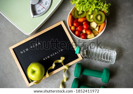 New Year for New Healthy 2021.  Fresh vegetable salad and healthy food for sport equipment for women diet slimming weight loss background. Healthy change new life Concept #1852411972
