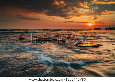 Beautiful seascape. Sunset scenery background. Moving waves. Low tide at the beach. Composition of nature. Motion water. Cloudy sky with sunlight. Slow shutter speed. Mengening beach, Bali, Indonesia Royalty-Free Stock Photo #1852440793