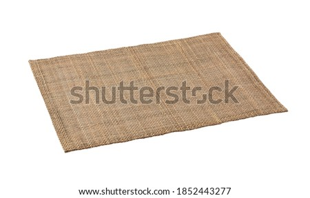 A woven luncheon mat on a white background. View from an angle