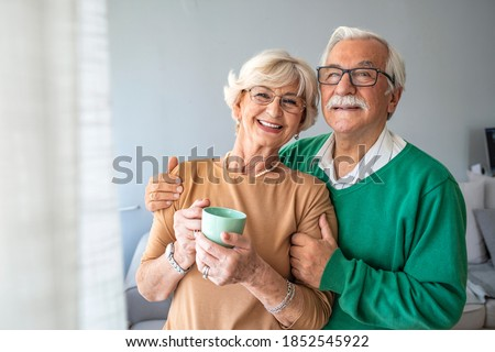 Happy senior man embracing woman in front of windows at home. Senior couple smiling and happy at home. Happy pensioner couple enjoying time at home