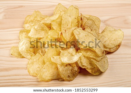 potato chips. pile of potato chips on a wooden table. Crispy potato chips. junk food concept. Fast food