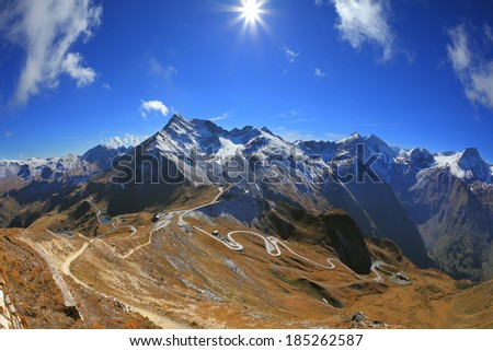 The picture was taken Fisheye lens. Austrian Alps. Excursion to the picturesque panoramic way Grossgloknershtrasse. Sunny day in early autumn. Great highway winds between hillsides yellowed