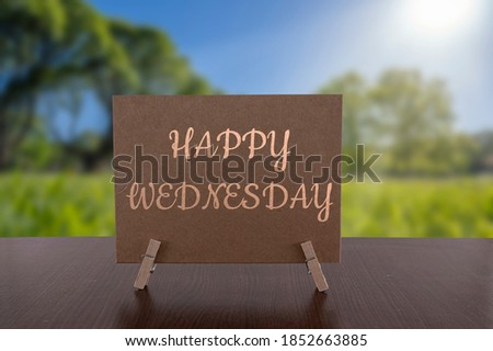 Happy Wednesday card on the table with sunny green forest background. Royalty-Free Stock Photo #1852663885