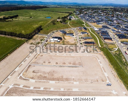 Aerial shots of a developing housing estate in the outer suburbs of Melbourne Australia, roads and gutters have been built, plots of land some already sold are almost ready for houses to be built. Royalty-Free Stock Photo #1852666147