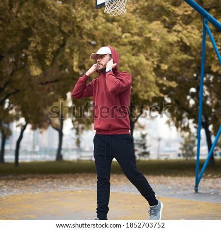 Athletic sporty man training in hoodie sweatshirt in urban city park / basketball court.