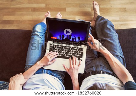 couple watching live streaming online concert at home