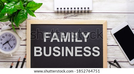 FAMILY BUSINESS written on a black background near pencils, a smartphone, a white notepad and a green plant in a pot