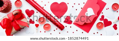 Banner. Valentine's Day. Flat lay of red hearts, handmade gift boxes, red roses and a notebook for writing on a white background. Copy space. The concept of holidays and love.