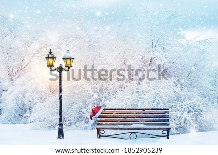 Christmas fabulous image. Lantern, bench and cap of Santa Claus in the winter city park. Winter landscape. Royalty-Free Stock Photo #1852905289