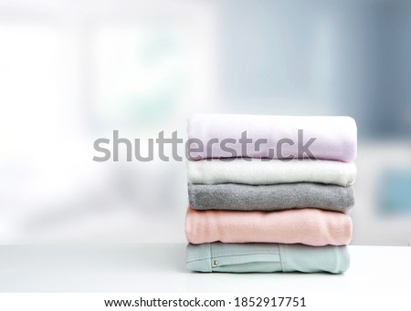 Soft colors stack of clothing,clothes folded on table empty copy space background.Colorful garment stacked. Royalty-Free Stock Photo #1852917751