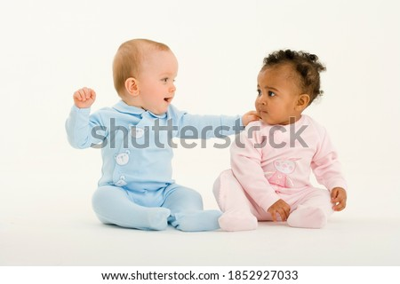 Horizontal shot of a seated baby boy and girl looking at each other with the boy's hand on girl's shoulder. Royalty-Free Stock Photo #1852927033