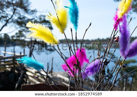Swedish Easter birch twigs decorated with colorful feathers in yellow, blue, purple and pink and a few Easter chicken decorations. In the background is the Swedish archipelago and Baltic sea. Royalty-Free Stock Photo #1852974589