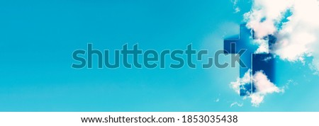 Shining cross in clouds on blue sky. Copy space. Ascension day concept. Christian Easter. Faith in Jesus Christ. Christianity. Church worship, salvation concept. Gate to heaven. Eternal life of soul.
