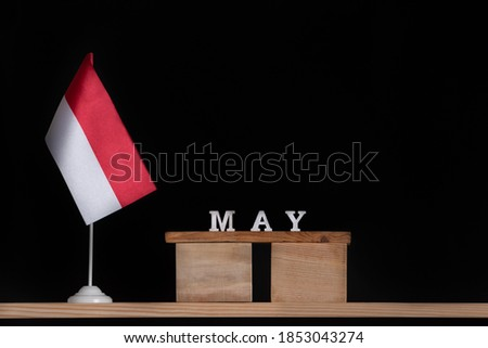 Wooden calendar of May with Polish flag on black background. Holidays of Poland in May