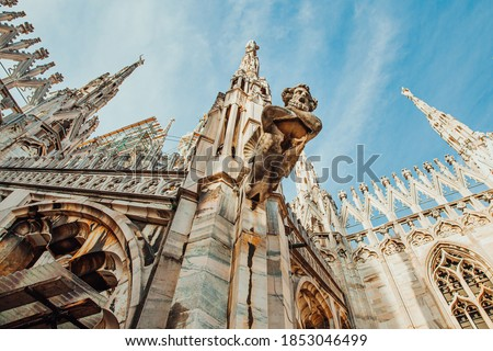 Roof of Milan Cathedral Duomo di Milano with Gothic spires and white marble statues. Top tourist attraction on piazza in Milan, Lombardia, Italy. Wide angle view of old Gothic architecture and art #1853046499