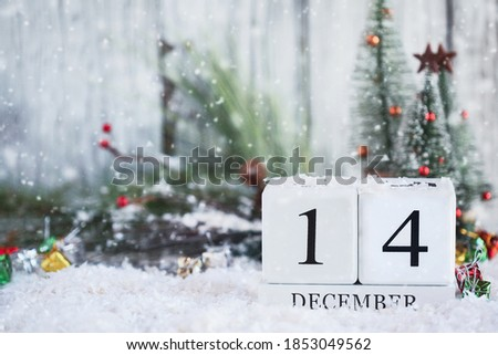 White wood calendar blocks with the date December 14th and Christmas decorations with snow. Selective focus with blurred background.
