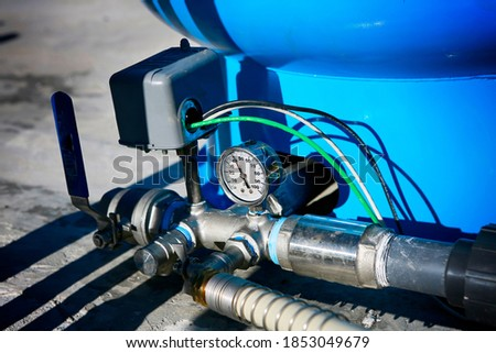 Deep water well set up. Water pressure gauge and storage tank. Royalty-Free Stock Photo #1853049679