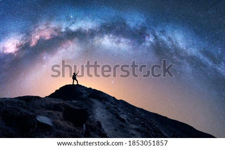 Arched Milky Way and happy man on the mountain at night. Silhouette of guy with raised up arm on the hill, sky with stars, yellow light in Nepal. Galaxy. Space landscape with milky way arch. Travel Royalty-Free Stock Photo #1853051857