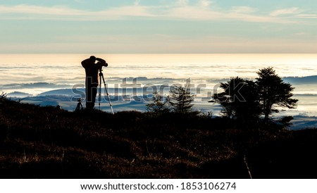 Silhouette of a photographer taking picture from a tripod early in the morning with good light on an inversion day, Jeseniky, Czech Republic.