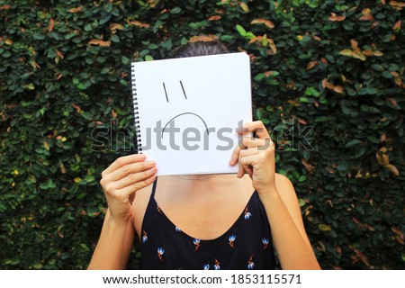 Young woman holding a notebook with a sad face draw, in front of her own face. Sadness representation.