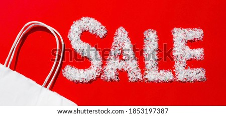 Banner. Seasonal sale, Black Friday, new year discounts and shopping concept. Sale sign and a paper shopping bag on a red background. Flat lay.