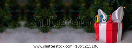 Blurred seamless patterned new year and Christmas banner with red gift box and game chips: Christmas tree branches with bright blurred lights on the snow, bokeh of holiday lights, space for text