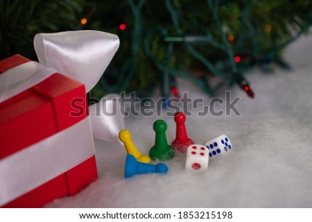 Red gift box with white ribbon next to four game chips of different colors and dice on white snow on background of Christmas tree shining bright lights in form of bokeh: place for text, happy New Year