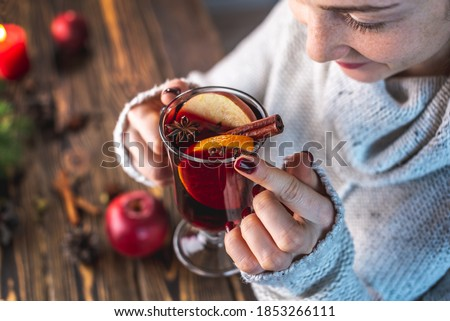 Girl in a warm sweater is holding a glass of mulled wine. Concept of a festive mood, a magical cozy atmosphere with a mug of traditional hot beverage. Royalty-Free Stock Photo #1853266111