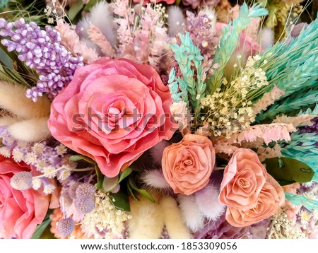 Closeup and crop colorful rose flowers and decorative of dry and paper artificial flowers in bouquet.