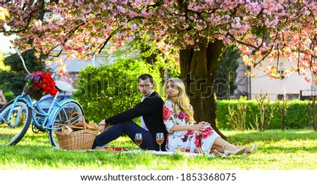 Happy loving couple relaxing in park with food. Enjoying their perfect date. Couple in love picnic date. Spring weekend. Romantic picnic with wine. Give uncommon, unique gifts spontaneously. Royalty-Free Stock Photo #1853368075