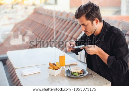 Young blogger man taking pictures of his food in a rooftop restaurant. A Burger, beer and french fries on the table