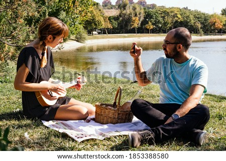 Couple sitting on tablecloth enjoying picnic, playing ukulele and taking pictures