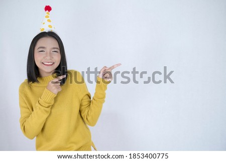 Beautiful girl wear yellow sweater, party hat and smiling, white backdrop.