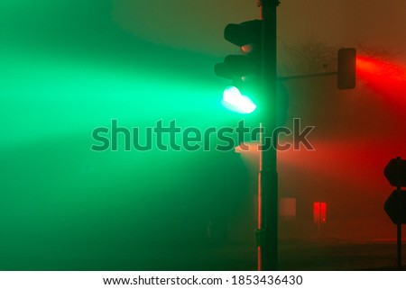 green and red traffic lights in a foggy night