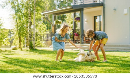 Two Kids Have fun with Their Handsome Golden Retriever Dog on the Backyard Lawn. They Pet, Play, Scratch it. Happy Pedigree Dog Holds Toy ball in Jaws. Idyllic Suburb House in the Summer Royalty-Free Stock Photo #1853535598
